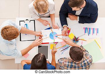 Discutiendo diagrama. La mejor vista de la gente de los negocios apuntando el diagrama mientras se sienta en la mesa