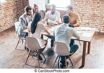 Discutiendo nueva estrategia. Un grupo de seis jóvenes discutiendo algo mientras están sentados en la mesa juntos