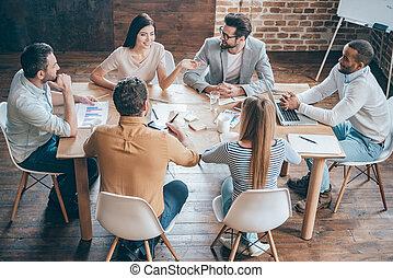 Discutiendo nuevas posibilidades. La mejor vista de los jóvenes empresarios discutiendo algo mientras están sentados juntos en la oficina