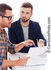 Discutir proyecto. Dos personas de negocios seguras en ropa informal elegante se sientan juntos en la mesa y discuten algo