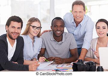 Discutir un nuevo proyecto juntos. Un grupo de alegres empresarios sentados juntos en la mesa y discutiendo algo