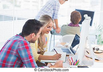 Diseños alegres trabajando en un documento