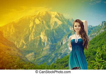 Disfrútalo. Una joven con el pelo largo, sobre montañas rocosas
