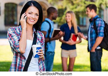 Disfrutando de la vida estudiantil. Hermosa joven hablando por teléfono móvil y sonriendo mientras se enfrenta a la universidad con sus amigos charlando en el fondo