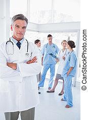 Doctor con brazos cruzados frente a su equipo médico