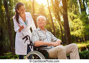 Doctor hablando con el viejo en silla de ruedas