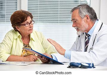 Doctor hablando con su paciente femenina