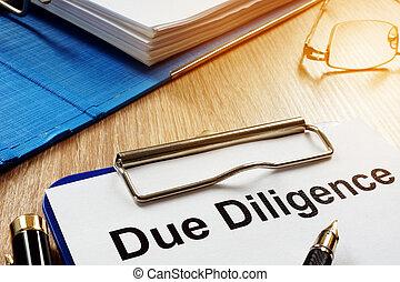 Documento con el título de Due Diligence en un escritorio.