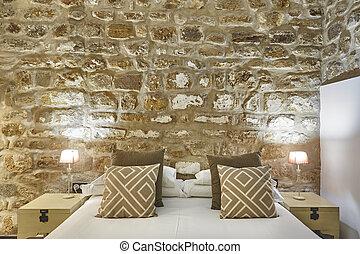 Dormitorio con paredes de piedra. La cómoda habitación de hotel moderno. Interior