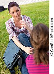 Dos amigas hablando juntas sentadas en la hierba