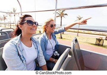 Dos amigos tomando el autobús de la ciudad de gira por el pueblo