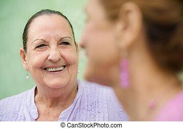Dos ancianas se reúnen y hablan en el banco del parque