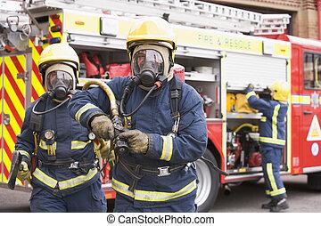 Dos bomberos con mangueras y hachas que se alejan de los motores de fuego y de otro bombero de fondo.