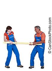Dos carpinteros con tabla de madera
