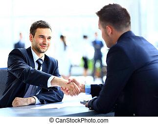 Dos colegas de negocios estrechando la mano durante la reunión
