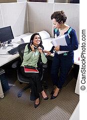 Dos colegas hispanos se encuentran en el cubículo de la oficina