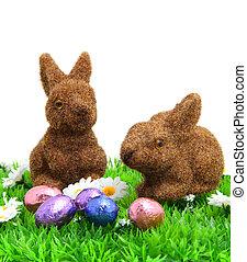 Dos conejitos marrones en la hierba con huevos de Pascua
