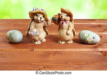 Dos conejos de pascuas en madera con huevos decorativos