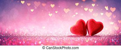 Dos corazones con brillo rosa en el fondo brillante - concepto del día de San Valentín
