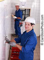 Dos electricistas trabajando en el baño