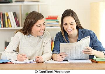 Dos estudiantes felices leyendo un periódico
