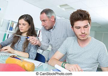 Dos estudiantes trabajando con el profesor