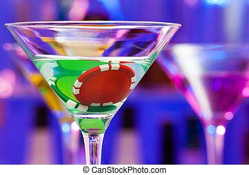 Dos fichas de casino en el cóctel del bar