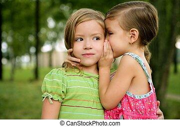 Dos hermanitas gemelas susurran al oído