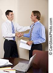 Dos hombres de negocios en la oficina estrechando la mano