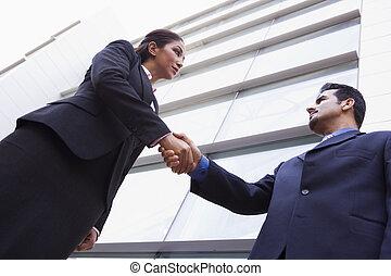 Dos hombres de negocios estrechando la mano fuera del edificio de oficinas