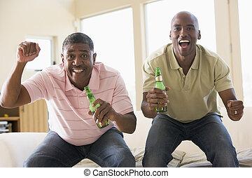 Dos hombres en el salón con botellas de cerveza vitoreando y sonriendo