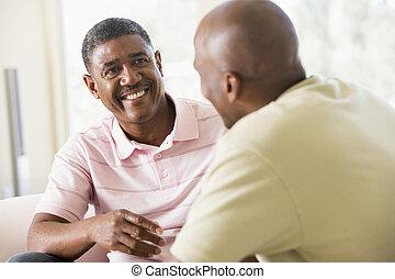 Dos hombres en el salón hablando y sonriendo