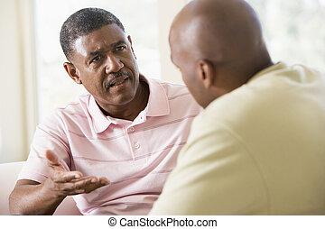 Dos hombres en la sala de estar hablando