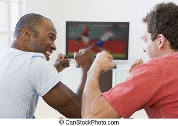 Dos hombres en la sala de estar mirando televisión y vitoreando