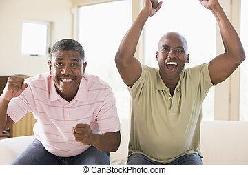 Dos hombres en la sala vitoreando y sonriendo