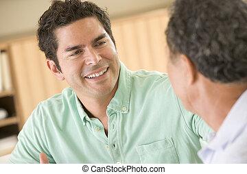 Dos hombres sentados en el salón hablando y sonriendo