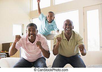 Dos hombres y un joven en la sala vitoreando y sonriendo