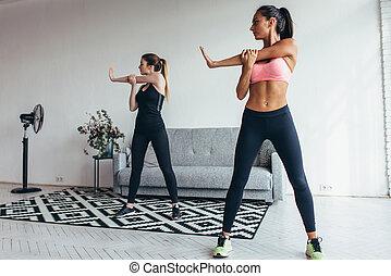 Dos jóvenes en forma estirando sus brazos ejercitándose en casa. Modelos de físico femenino caucásicos funcionando por la mañana.