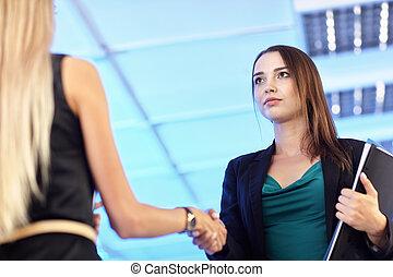 Dos jóvenes en la oficina con carpetas con papeles se dan la mano