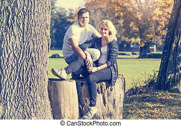 Dos jóvenes enamorados sentados en un bosque