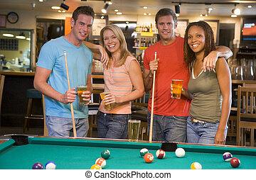 Dos jóvenes parejas de pie junto a una mesa de billar en un bar