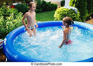 Dos lindas y alegres hermanitas jugando y divirtiéndose, chapoteando y saltando en piscina inflable en el patio trasero