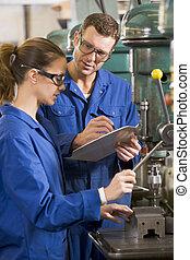Dos maquinistas trabajando en la máquina