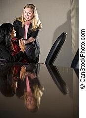 Dos mujeres de negocios hablando en la sala de juntas