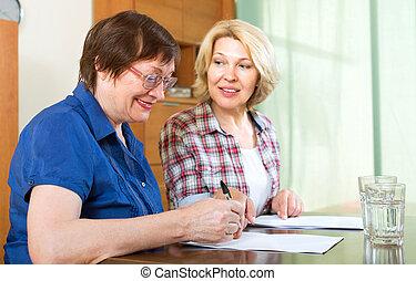 Dos mujeres firmando documentos en casa