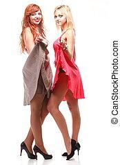 Dos mujeres guapas de jengibre con vestidos de blanco