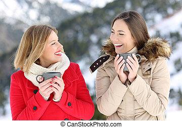 Dos mujeres hablando con tazas de café en invierno