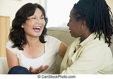 Dos mujeres hablando en el salón y sonriendo
