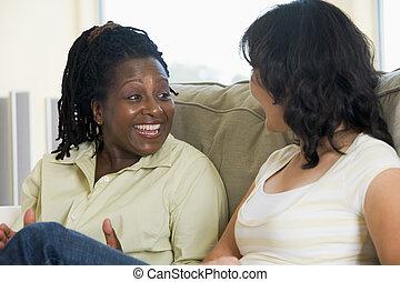 Dos mujeres hablando en la sala y sonriendo