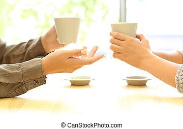Dos mujeres hablando en un bar con tazas de café